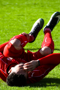 soccer player is lying on the ground holding his leg in pain