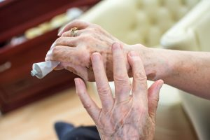 an older woman is rubbing topical pain relief ointment into her hand and wrist.